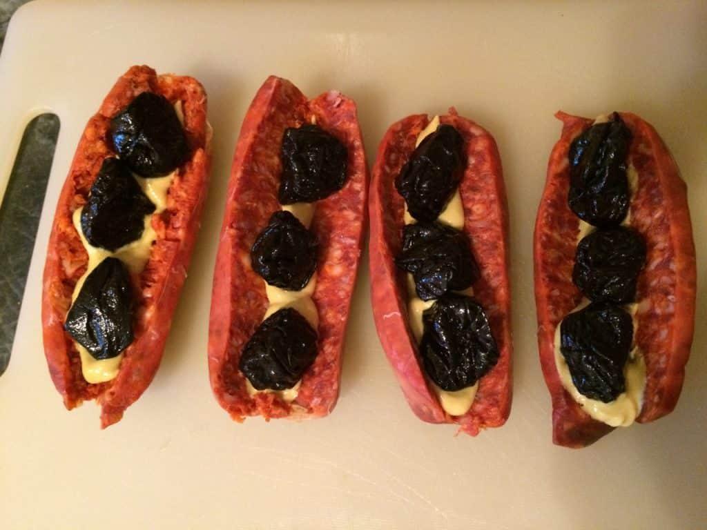 In die aufgeklappte Chorizo kommen scharfer Senf und Backpflaumen