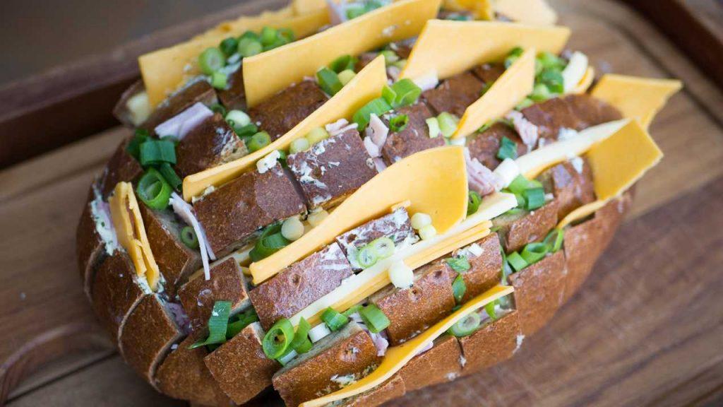 Kräuterbutter, Käse, Schinken und Lauchzwiebeln in die Einschnitte füllen.
